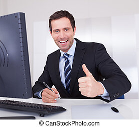 Portrait Of Happy Businessman Cheering At Workplace