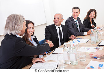 Two Mature Businessman Shaking Hands In Meeting