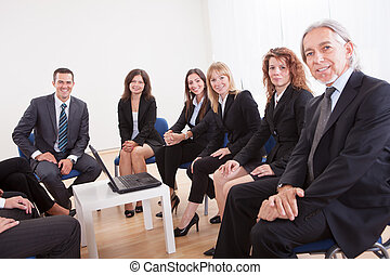 Group Of Business People Sitting On Chairs