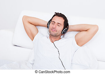 Young Man Listening Music On Headphone, Indoors