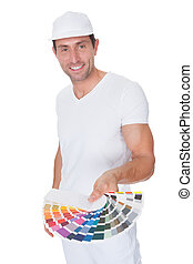 Painter Holding A Paint Roller And Spectrum Of Color Samples...