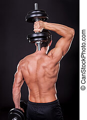 Young Man Exercising With Weightlift Isolated On Black...