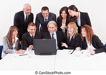Businessman Showing On Laptop In Meeting