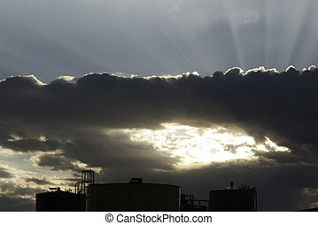 sun rays through clouds over industrial tanks - sun rays...