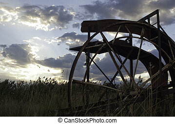 old farm equipment in field sunset