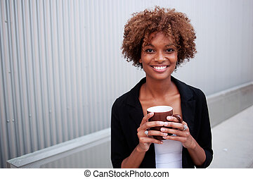 pretty African American executive with mug - portrait of a...