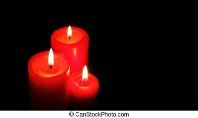 Three candle lights in the dark.