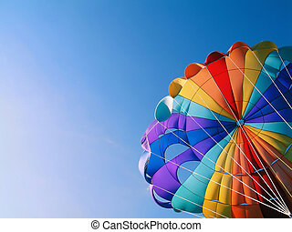 Parachute Detail - A colorful parachute with blue summer sky...