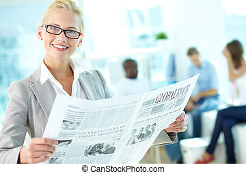Female reading newspaper - Portrait of happy female with...