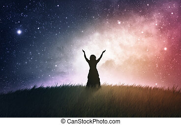 Worship at Night - A woman lifting her hands with a space...
