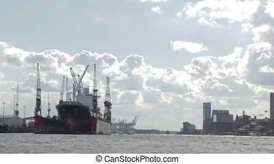 Cargo ship in Hamburg port. Bright backlit clouds.