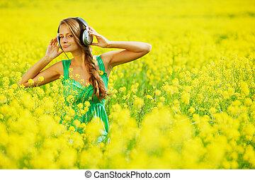 woman on oilseed field listening music