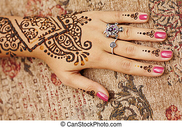 Henna art on womans hand - The Indian pattern is drawn a...