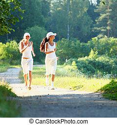 woman running - Beautiful young woman running in green park...