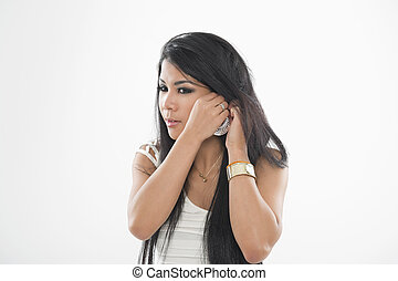 Woman putting on her earring - Attractive Asian woman...