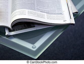 Open magazines on a glass table