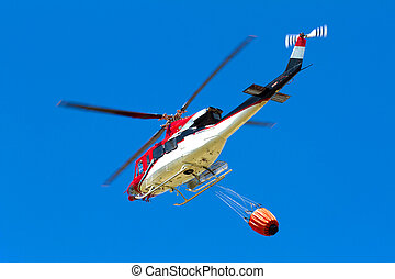 emergency helicopter extinguishes flames of a raging bush...