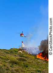 emergency helicopter extinguishes flames of a raging bush fire