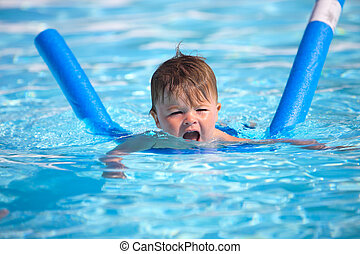 Happy little boy learning to swim with pool noodle
