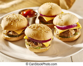 mini burgers with cheese, onion and pickle.