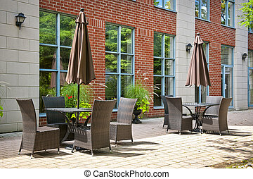Tables and chairs on outdoor patio - Patio furniture with...