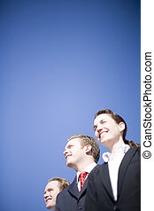 Business Vision - three happy business people looking in...