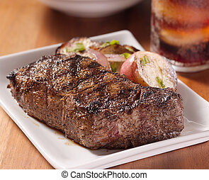 grilled steak with potatoes and cola in background.