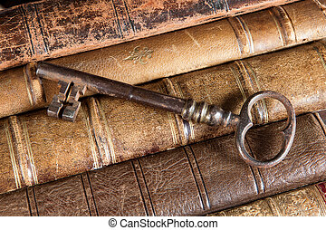 Rusty key on old books - Large rusty key lying on weathered...