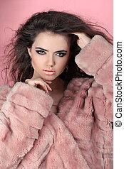 Winter Girl in Luxury Fur Coat over pink