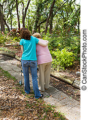 Teen Helping Senior - Teen girl helping senior woman walk...