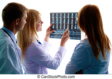 Discussing x-ray - Portrait of young doctor showing and...