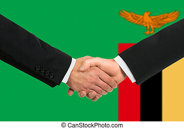 The Zambian flag and business handshake