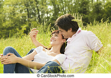 meadow - Couple lying in grass, man tickling her...