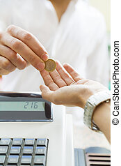 consumerism - man paying 1 euro to the cashier in a store....