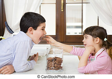 children - little girl in the kitchen giving a cookie to her...