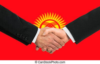 The Kyrgyz Flag and business handshake