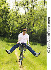 meadow - man biking in park, smiling and outstretching his...