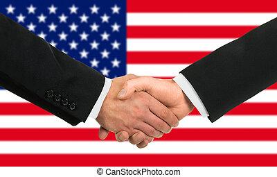 The USA flag and business handshake