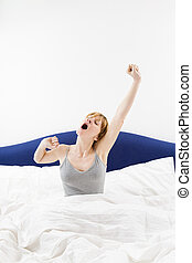 morning routine - Young woman sitting on bed, stretching...