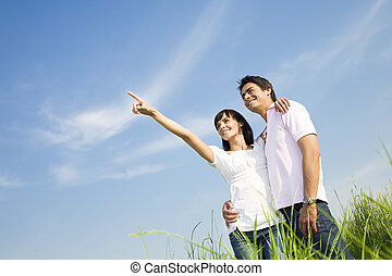 meadow - young couple in meadow with hand in air, hugging...