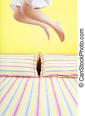 morning routine - young woman jumping on bed with striped...