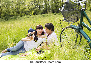 meadow - couple having a picnic in a park, smiling