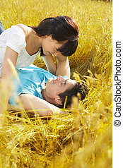 meadow - young couple laying down in meadow and hugging