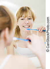 morning routine - Young woman looking into a mirror brushing...