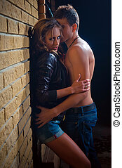 guy kissing his girlfriend against a wall at home - A shot...