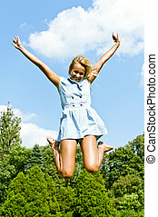 Beautiful young woman jump up to the sky in park