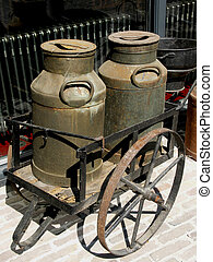 Milk jugs. - Old wheelbarrow carrying two old milk cans.
