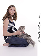 Pregnant woman with persian cat, studio shot on white...