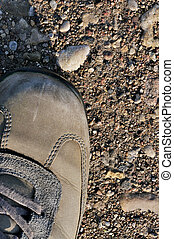 Hiking boot off-road shoe on hard arid dried soil, vertical close up, detailed macro of bare earth, dust, stones, rocks, pebbles, sand, ash