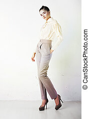 Pretty stylish girl in white trousers and blouse posing -...